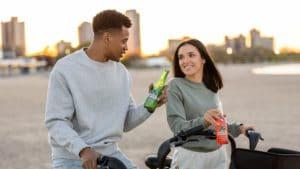 man in white sweater holding green bottle beside woman in white sweater riding on bicycle